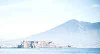 Looking at Mount Vesuvius from the Naples marina. Mount Vesuvius is very close to Naples so it makes for a great picture. According to Google Maps, that should be Ovo Castle in the foreground.